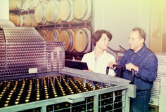 Wine maker showing bottles with wine. Wine maker showing to expert of bottles with a wine Stock Images