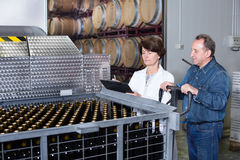 Wine maker showing bottles with wine. Wine maker showing to expert of bottles with wine Royalty Free Stock Photography