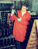 Wine maker taking care of seasoning bottles Royalty Free Stock Image