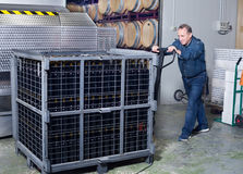 Wine maker unloads containers with bottles Stock Photos