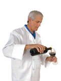 Wine maker. Winemaker or enologist pouring red wine into a glass, to sample his work isolated on white Royalty Free Stock Photos