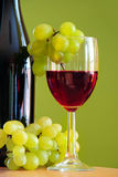 Wine making. Wineglass with red wine and green grapes cluster over green background Stock Image