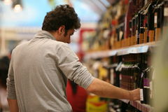Wine market. Customers shopping inside a supermarket - wine area in commercial center in Bucharest city, Romania Stock Photo