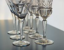 Wine and martini glasses set up in verticle rows on a reflective table top. Wine glasses and martini glasses are set up in diagonal rows for an event. This image stock images