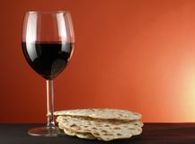Wine and matzoh. Glass of wine and matzoh ( jewish passover bread) over red background stock photography