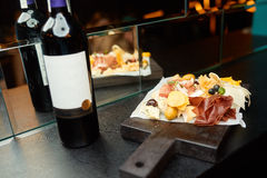 Wine with meat and cheese in a restaurant. On a wooden tray Royalty Free Stock Photo