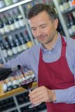 Wine merchant pouring glass red. Wine merchant pouring glass of red Stock Photography