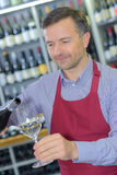 Wine merchant pouring glass wine. Wine merchant pouring glass of wine Stock Images