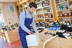 Wine merchant unpacking box wine. Wine merchant unpacking box of wine Stock Photo
