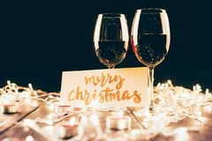 Wine and merry christmas card. Two glasses with red wine on wooden table with fairylights, candles and merry christmas card Stock Photography
