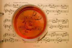 Wine and music. Old sheet music with goblet of wine shot from above Royalty Free Stock Photography