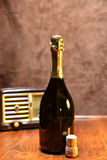 Wine and music. A retro style picture with a bottle of wine,a cork and an old radio on the background Stock Photography
