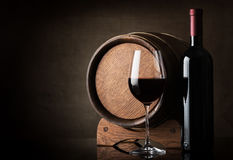 Wine near barrel. Red wine near wooden barrel on a brown background royalty free stock photography