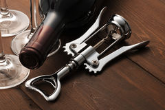 Wine and opener. On wooden table Stock Photography