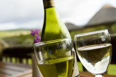 Wine at an outside restaurant. Glasses of white wine on a wooden table at an outside restaurant on a cloudy day in the countryside Royalty Free Stock Photos