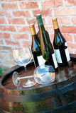 Wine over wood barrel. Glasses and bottles of wine over wooden barrel Stock Images