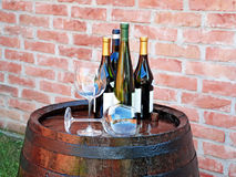Wine over wood barrel. Glasses and bottles of wine over wooden barrel royalty free stock photo