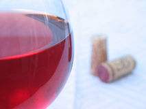 Wine Photo 1. A glass of wine in focus with corks out of focus royalty free stock photography