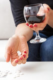 Wine and pills. A closeup of a woman holding a glass of wine and a handful of pills Royalty Free Stock Image