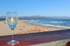 Wine at Plett. View of a white wine glass on a wood table overlooking massive blue ocean and sandy beach at Plettenberg Bay on the Garden Route, South Africa Stock Photography