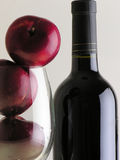 Wine and plums. Plums inside a cup and a bottle of wine royalty free stock image