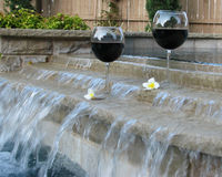 Wine and Pool. Set for a staycation with wine and plumeria petals in the backyard pool and suana stock images