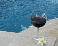 Wine and Pool. Set for a staycation with wine and plumeria petals in the backyard pool and suana royalty free stock photography