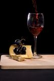 Wine poured. Red wine being poured in a glass, with bread, cheese and grapes Royalty Free Stock Image