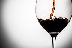 Wine poured into clear goblet on gray background Stock Photo