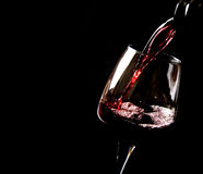 Wine. Poured on a glass - Black background Stock Image