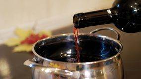 Wine is poured into the pot. Cooking traditional drink for Christmas. Mulled wine preparations stock video footage