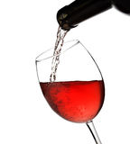 Wine is pouring from bottle into a glass isolated. On white Royalty Free Stock Image