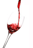 Wine Pouring into Glass. Red wine pouring into a glass, vertical on white background Royalty Free Stock Photo