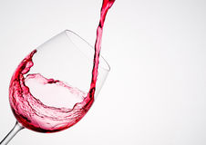 Wine pouring into a glass in diagonal composition. And white background royalty free stock image
