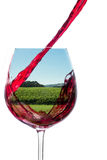 Wine pouring into a glass with a vineyard image in the glass, on Stock Photos