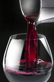 Wine pouring2. Photo of jar with wine being poured into nice glass. closeup studio photo on black background Stock Image