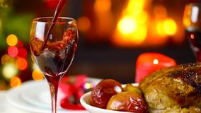 Wine pouring to glass on christmas table in front of fireplace. Slow motion stock footage