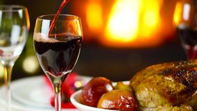 Wine pouring to glass on christmas table in front of fireplace. Slow motion stock video footage