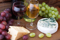 Wine pouring into wine glass. Cheese, grapes in Royalty Free Stock Photo