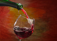 Wine pours into the glass of the bottle