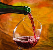 Wine pours into the glass of the bottle Stock Photography