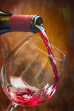 Wine pours into the glass of the bottle Stock Photo