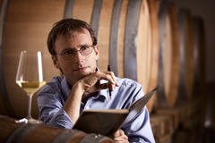 Wine producer contemplating in cellar. Winemaker contemplating over white wine creation during wine tasting and taking notes in wine cellar with barrels in Royalty Free Stock Images