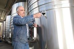 Wine producer stood by tanks stock photos