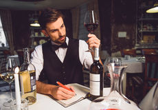 This wine is quite well. Sommelier is sitting near table and attentively looking at glass of crimson drink Stock Photo