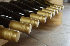 Wine on a rack. Nine bottles of identical wine in a wooden rack, on a tiled floor stock image