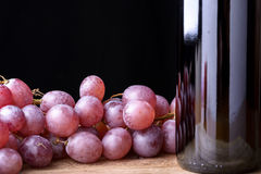Wine and red grapes. Bottle of red wine with bunches of red grapes on wooden table Stock Photos