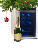 Wine refrigerator and bottle of champagne under Christmas tree. Stock Photos