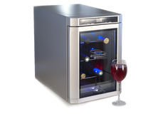 Wine refrigerator and glass of red wine. Royalty Free Stock Image