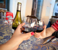 Wine at a restaurant. Two glasses of wine hold by a couple at the restaurant Stock Image